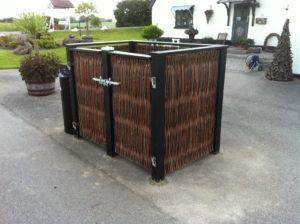 En meget smukt pilehegn opført med lodrette pilesektioner og en dobbelt smedejernslåge til affaldsstativerne.